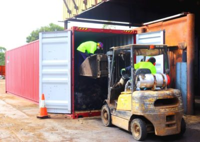 scrap items being loaded into a container to export